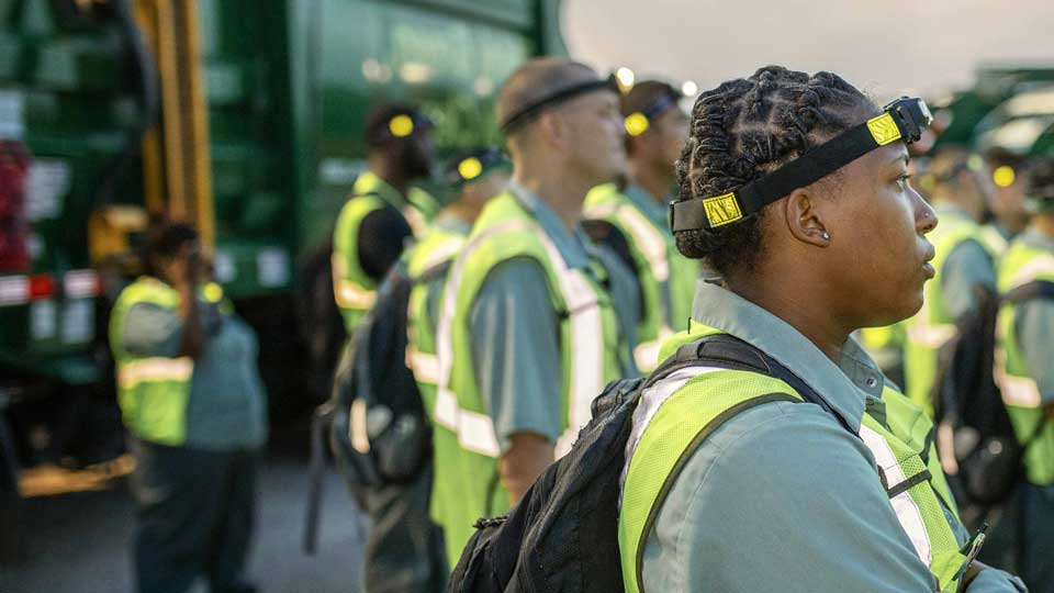 solid waste collection workers standing by a garbage truck